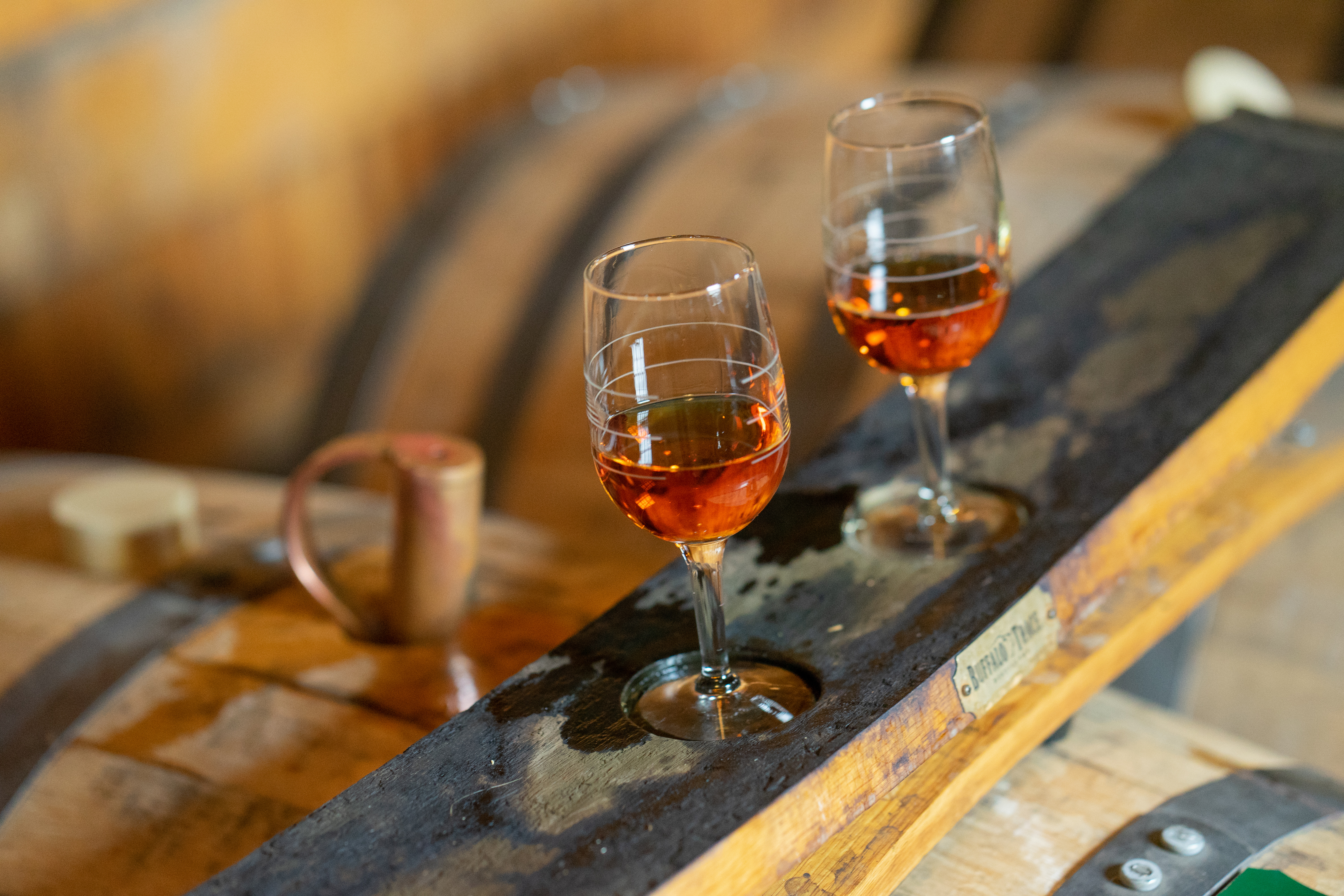 Two glasses of whiskey on barrels