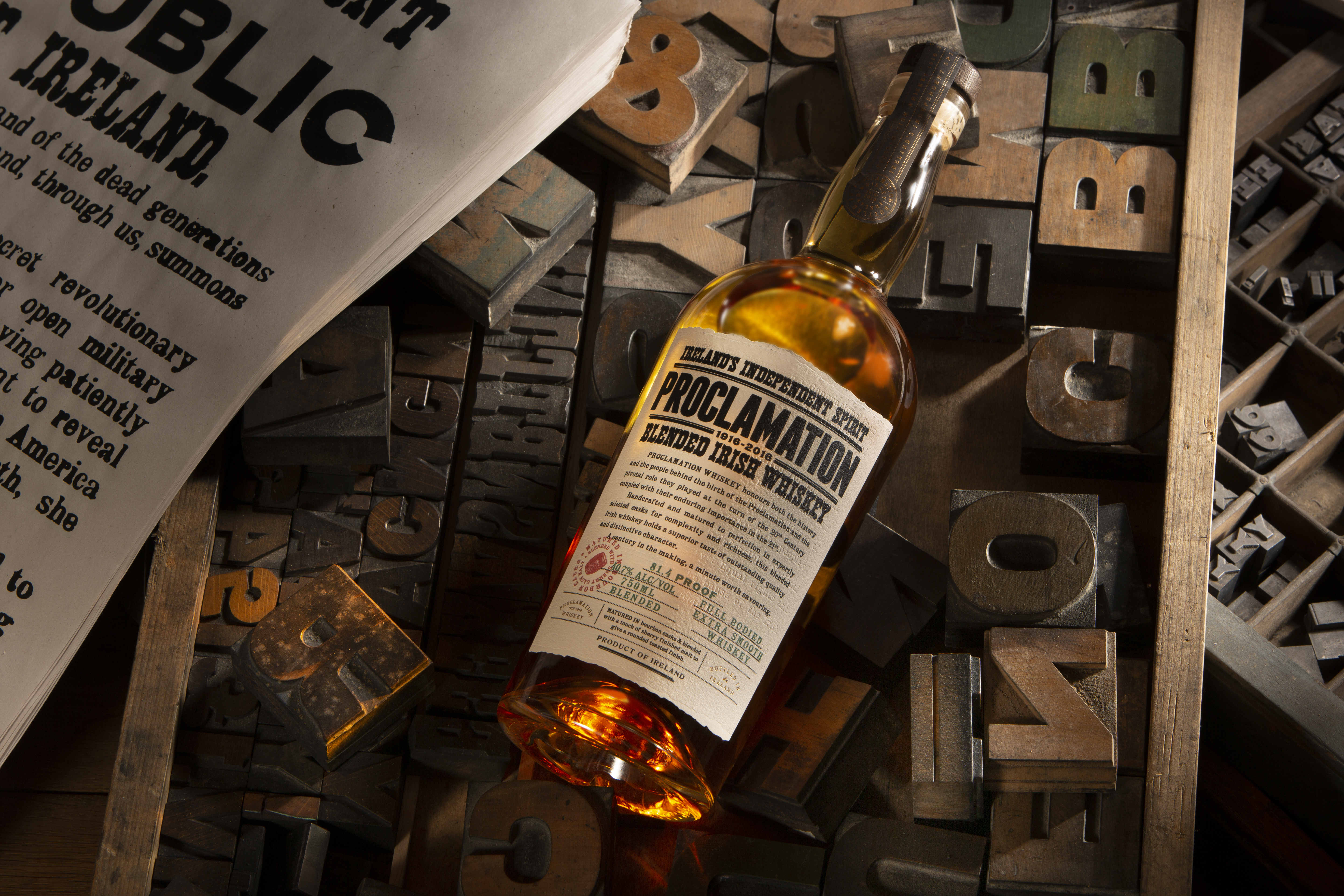 Proclamation whiskey bottle on top of printing materials